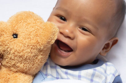 Cute african baby laughing and holding a teddy baby