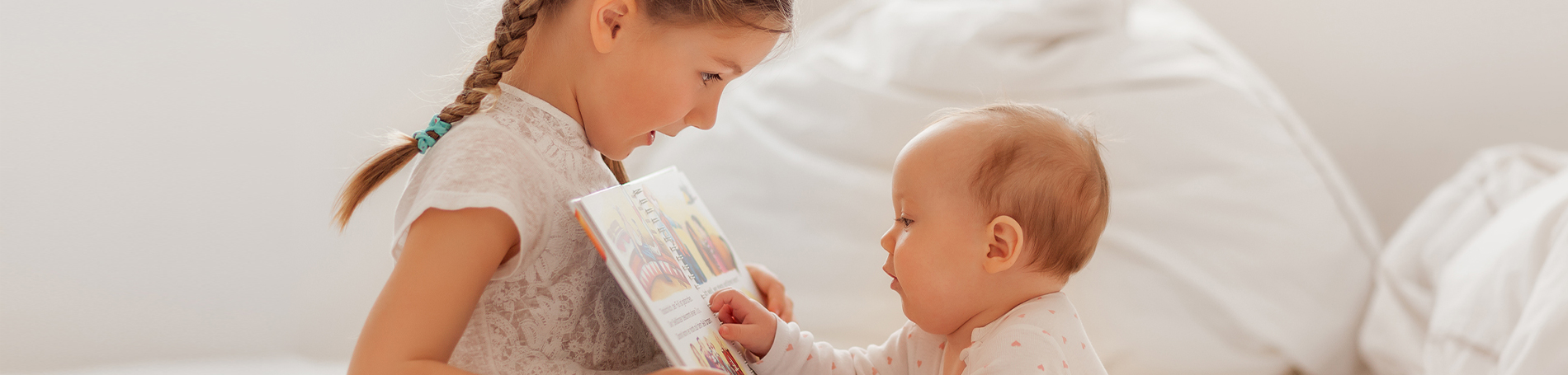 Little girl with plats showing her baby brother a book