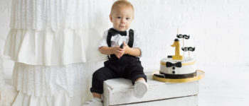 Little boy in party clothes sitting on a wooden box with a 1 year old birthday cake beside him