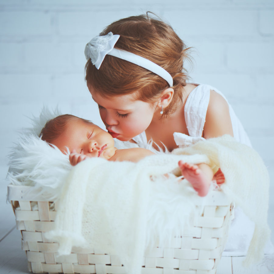 Toddler girl with a white hairband and a white dress kissing a very newborn looking baby who is sleeping on a fluffy white blanket in a crib