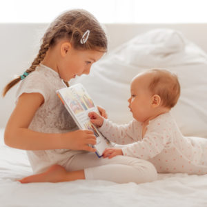Lttle girl sitting on a bed and showing her baby sister the pictures in a book