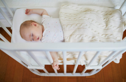 Baby fast asleep on her back in the cot veiwed from above