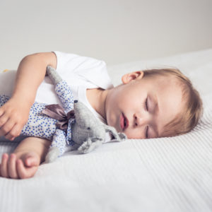 Litte boy sleeping on his side on a bed with a soft toy mouse in his arms