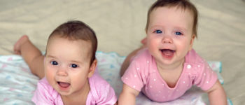 Twin baby girls smiling whilst playing on thier tummies