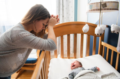 Stressed, sleep deprived mother with her head in her hands leaning on a cot with a one month old baby crying in the cot