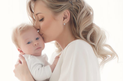 Elegant blond mother holding her young baby and kissing his head