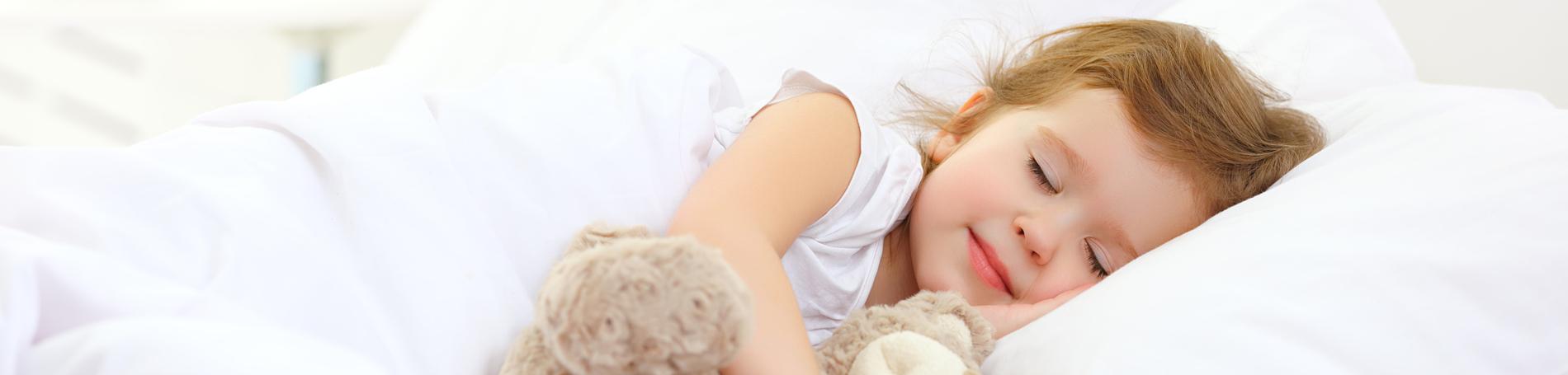 Little girl smiling in her sleep and cuddling her teddy bear