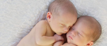 Newborn babies curled up and sleeping together on a soft white blanket