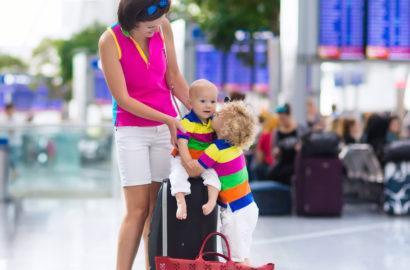 Mother with 5 year old child and a 1 year old baby sitting on a suitcase at the airport