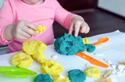 Childs hands playing with homemade green and yellow coloured playdough and a plastic knife and spoon on the table