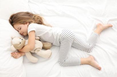 5 year old sleeping girl in bed cuddling a teddy bear