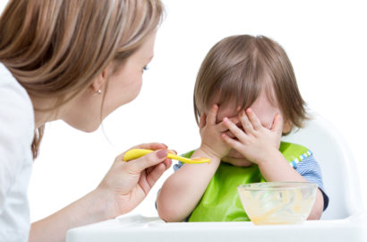 Mother trying to spoon feed her toddler who has his hands in front of his whole face as if he is refusing to eat
