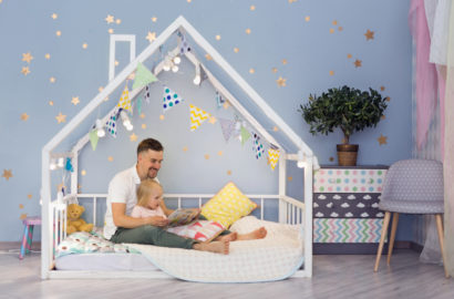 Father and 3 year old daughter in a framed toddler bed with the mattress at floor level. Stars on the wall and colourful flags attached to the frame of the bed which goes up and over the childs head in the shape of a house.