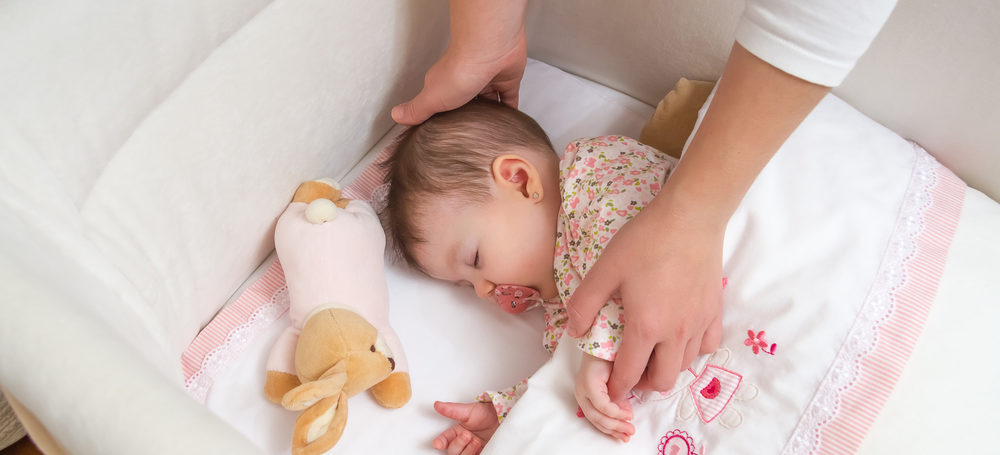 Baby in a crib with a dummy in her mouth and the mothers hands soothing her whilst she settles to sleep