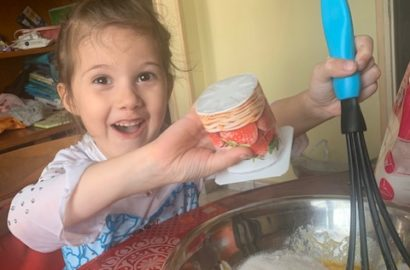 4 year old little girl looking excited whilst putting ingredients into a bowl with the use of a yogurt pot and a whisk in a bowl.